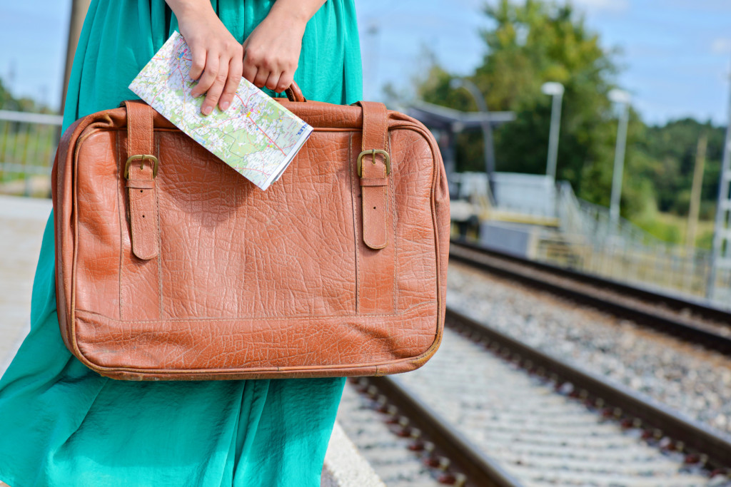 Womans hands holding a map and suitcase at station